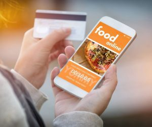 a woman ordering food online using her phone and her credit card
