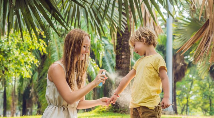 a mom and her son out in the grass as she sprays bug spray on him