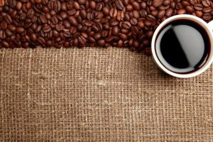 coffee beans on a linen surface with a cup of coffee