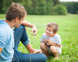 a father having a discussion with his son in the park