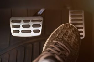 a close up of a tennis shoe reaching for the gas pedal