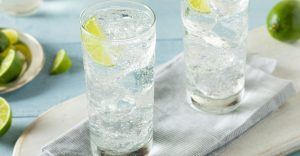 two glasses of sparkling water with lime wedges on a tabletop