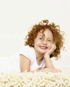 a little girl with red, curly hair posing on the carpet