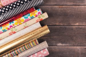 rolls of colourful wrapping paper side by side on a wooden tabletop