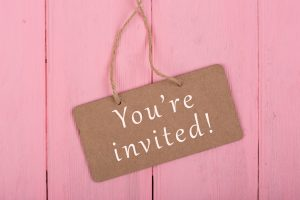 """a gift tag reading, """"you're invited' on a pink wooden background"""