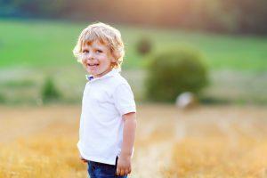 a blonde toddler boy in a wheat field