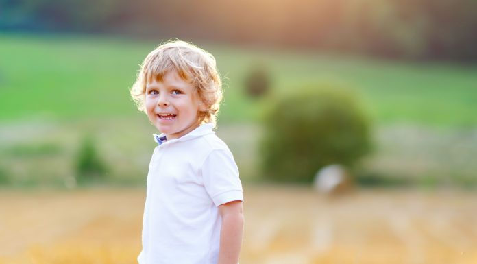 a blonde toddler boy in a wheat field
