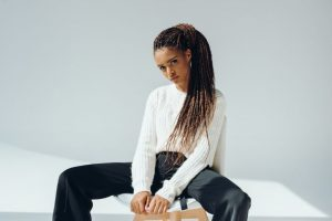 a fashionable African American woman in a white shirt with black pants sitting on a stool
