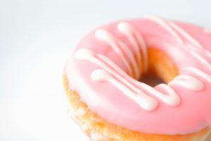 a pink iced donut on a white background