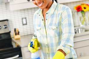 an African American woman wearing yellow rubber gloves as she cleans the kitchen counter
