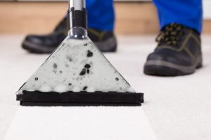 a close up of a man's feet and a carpet cleaning vacuum as he cleans an off white carpet