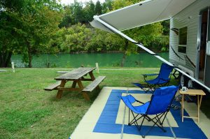 the canopy of an RV with chairs and a picnic table by a lake