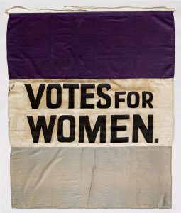 a banner with the words, Votes for Women as Kamala Harris runs as the first black woman for Vice President