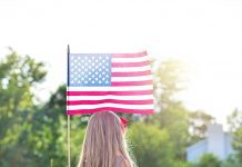 a photo taken of the back of a young girl as she stands in a field, holding the American flag