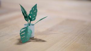 summer crafts of a toilet paper roll with a plant coming out of it on a wooden tabletop