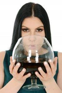 a close up of a brunette woman in a green dress drinking from a giant wine glass