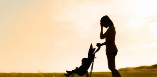 a silhouette of a mom pushing a stroller down a grassy road, with her hand to her forehead in stress