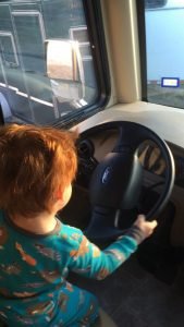 a toddler with auburn hair holding the steering wheel while pretending to drive