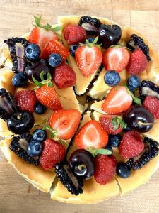a close up of a cheesecake covered in strawberries and blueberries