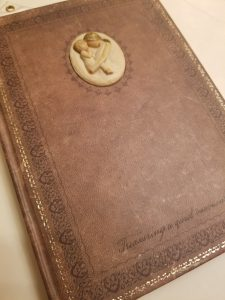 an old, brown, leather bound journal repurposed into a maternity journal