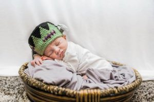 a photo of a newborn baby boy in a basket with a knitted Frankenstein cap as he was born on Friday the 13th