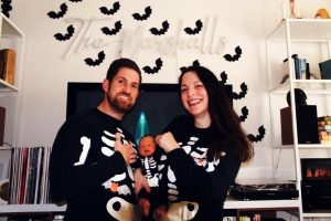 a dad, mom, and baby all wearing black Halloween pajamas with skeletons on them