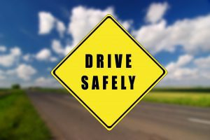 """a yellow """"drive safely"""" sign in the forefront, with a blurred road in the background"""