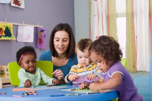a teacher and three toddlers sitting a table coloring in daycare