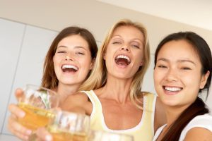 three moms standing together as the toast with their glasses of wine