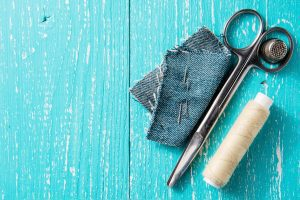 a pair of scissors, a thimble, white thread, and a few needles poked through a square of denim on a distressed turquoise wooden background