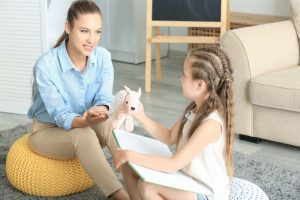 a girl with a stuffed animal talking with a child therapist
