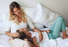 a daughter laying with her head in her mom's lap as the mom sits propped up in bed