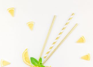 a lemon slice with straws stuck in it, with little lemon wedges in the background