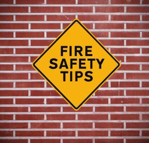"""a yellow diamond sign with the words, """"Fire Safety Tips"""" hanging on a red brick wall"""