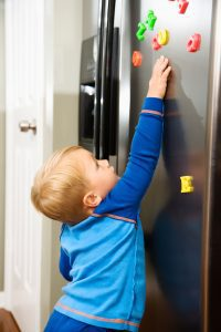 a toddler playing with alphabet magnets on the refrigerator