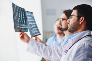 doctors looking at x-rays of central spinal stenosis