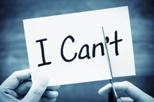 """a black and white photo of the words, """"I Can't"""" on an index card with two hands, cutting off the """"t"""""""