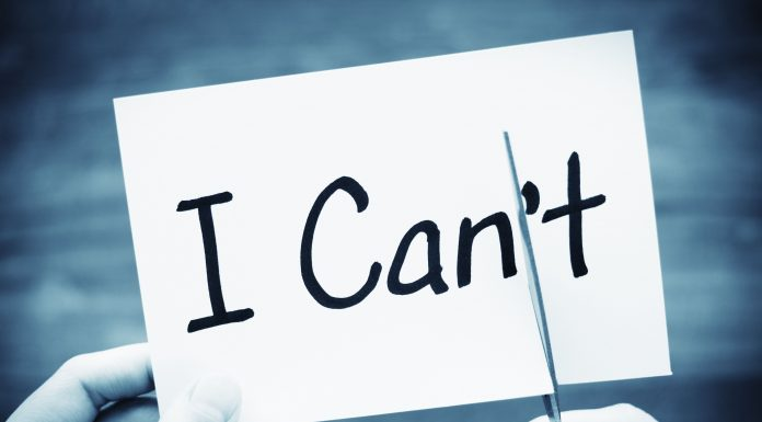 "a black and white photo of the words, ""I Can't"" on an index card with two hands, cutting off the ""t"""