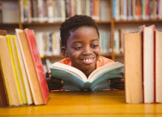 an African American boy smiling as he reads a book in the library