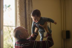 a grandpa holding his infant grandson up in the air