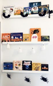 three white wall bookshelves filled with Halloween books, with bats, ghosts, and spiders decorating the shelves