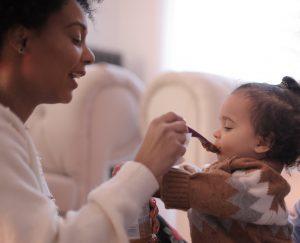 a mom spoon feeding her baby