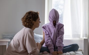 a teenager sitting cross legged on her bed with her hood on, the strings pulled tight to close it as her mom tries to talk to her