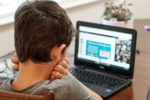 a boy sitting in front of a computer screen