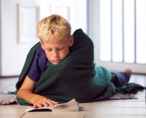 a boy wrapped in a blanket as he lays on the floor reading