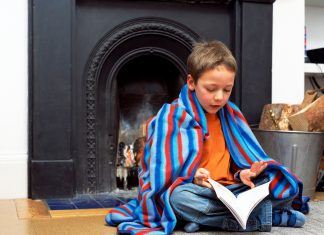 a boy wrapped in a blanket sitting in front of the fireplace with a book