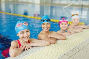 four girls hanging on the edge of a pool wearing swim caps and goggles