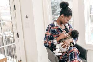 An African American woman sitting in a chair by the window as she breastfeeds her baby