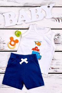 a baby boy's outfit of navy shorts and a white sleeveless onesie on a whitewashed background with a pacifier and the word BABY in white wooden letters