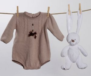 a knitted tan baby girl long sleeved onesie on a clothesline next to a bunny hanging from the clothesline by his ears